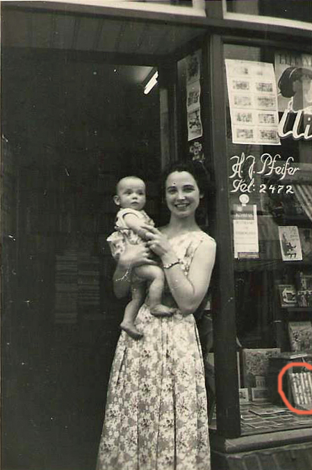 De winkel van Zef Pfeifer aan de Sittardse Steenweg in 1958. Op de voorgrond Rosie, dochter van Zef, met op haar arm haar zoon Jos Köhlen. Rechts in de benedenhoek is in de etalage een postzegelpakket te zien. Jos Köhlen stelde de foto ter beschikking.